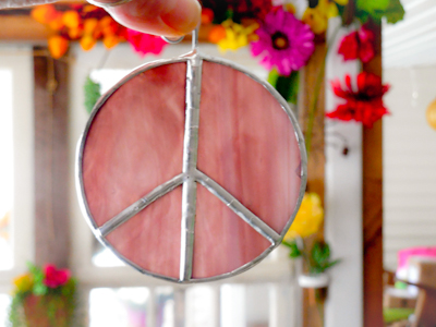 purple stained glass peace signs with flowers in the background