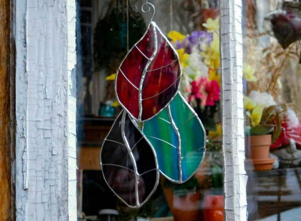 Stained glass leaf suncatchers hanging in an old window.
