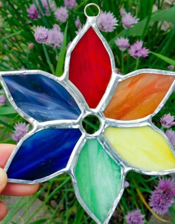 Rainbow colored stained glass flat pinwheel style flower.