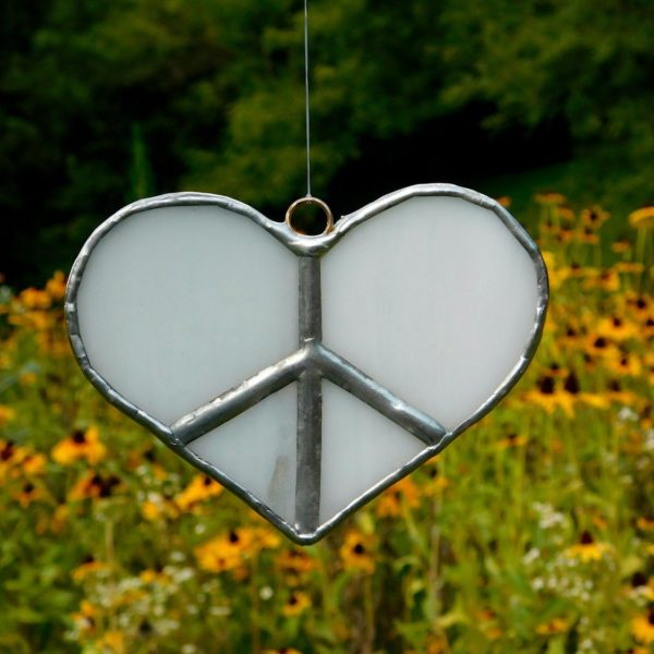 White stained glass heart peace sign suncatcher hanging in front of field of flowers