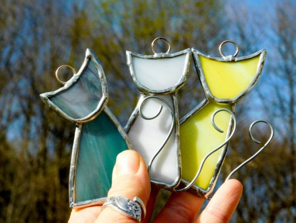 Photo of stained glass cat suncatchers in blue, white and yellow